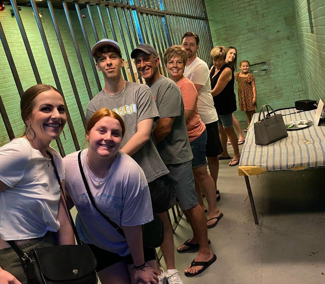 Family posing inside The Row escape room.